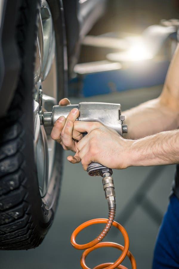 Mechaniker, der Autorad durch pneumatischen Schlüssel schraubt oder abschraubt lizenzfreie stockfotos