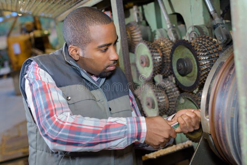 Mechaniker, der Bemühung verwendet, Schlüssel auf Maschinerie tuen stockbilder