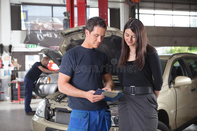 Mechaniker, der die Kosten des Services zeigt stockfotos