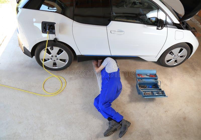 Mechaniker, der ein elektrisches gefahrenes Auto an der Garage repariert stockbilder