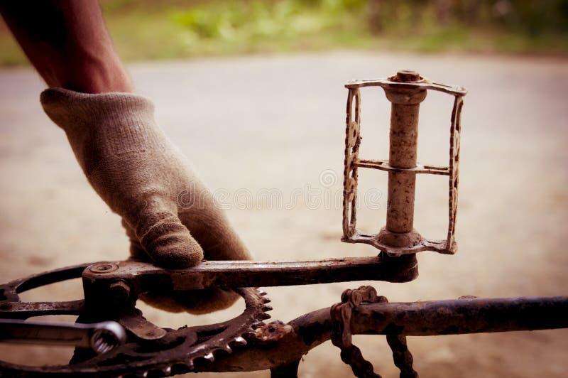 Mechaniker, der ein Fahrrad, ein Chainring und Pedale repariert lizenzfreies stockfoto
