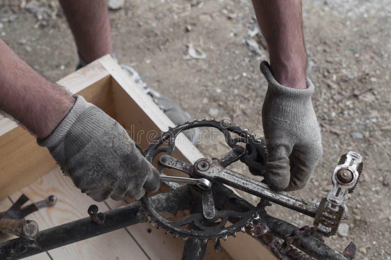 Mechaniker, der ein Fahrrad, ein Chainring und Pedale repariert lizenzfreie stockbilder