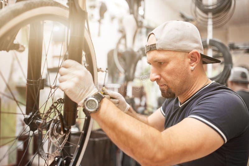 Mechaniker, der eine Mountainbike in einer Werkstatt repariert lizenzfreies stockbild