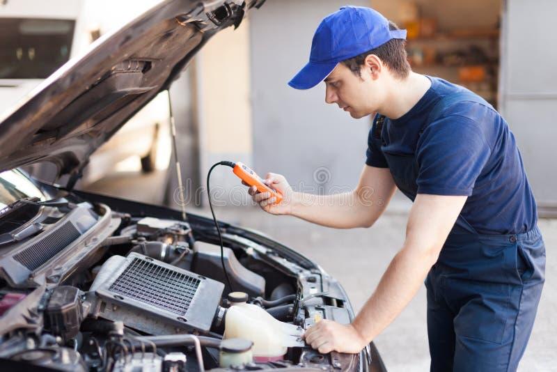 Mechaniker, der eine Prüfvorrichtung auf einem Automotor verwendet stockbild