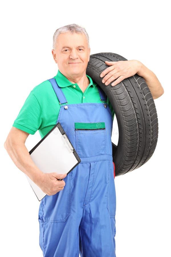 Mechaniker, der einen Fahrzeugreifen und ein Klemmbrett hält stockbild