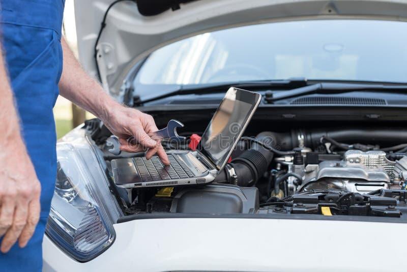 Mechaniker, der Laptop für die Prüfung des Automotors verwendet stockbild