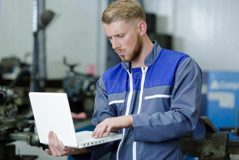 Mechaniker, der Laptop f?r die Pr?fung des Automotors verwendet lizenzfreie stockfotos