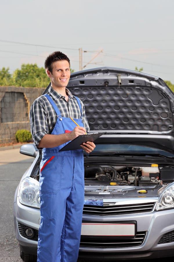 Mechaniker, der nahe bei einem Auto mit geöffneter Haube steht stockfotos