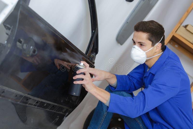 Mechaniker, der Spray mit Farbe für malendes Auto verwendet stockbilder