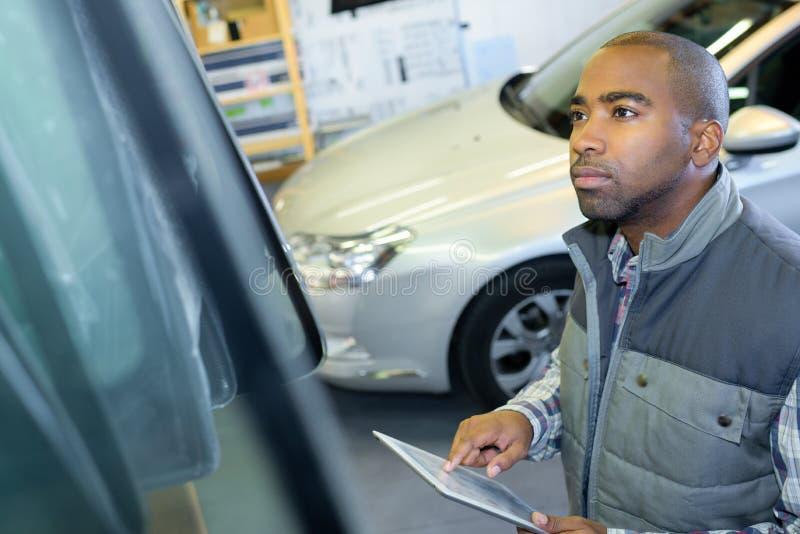 Mechaniker, der Tablette an der Reparaturgarage verwendet lizenzfreie stockfotos