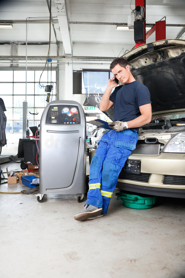 Mechaniker, der am Telefon spricht stockfotografie