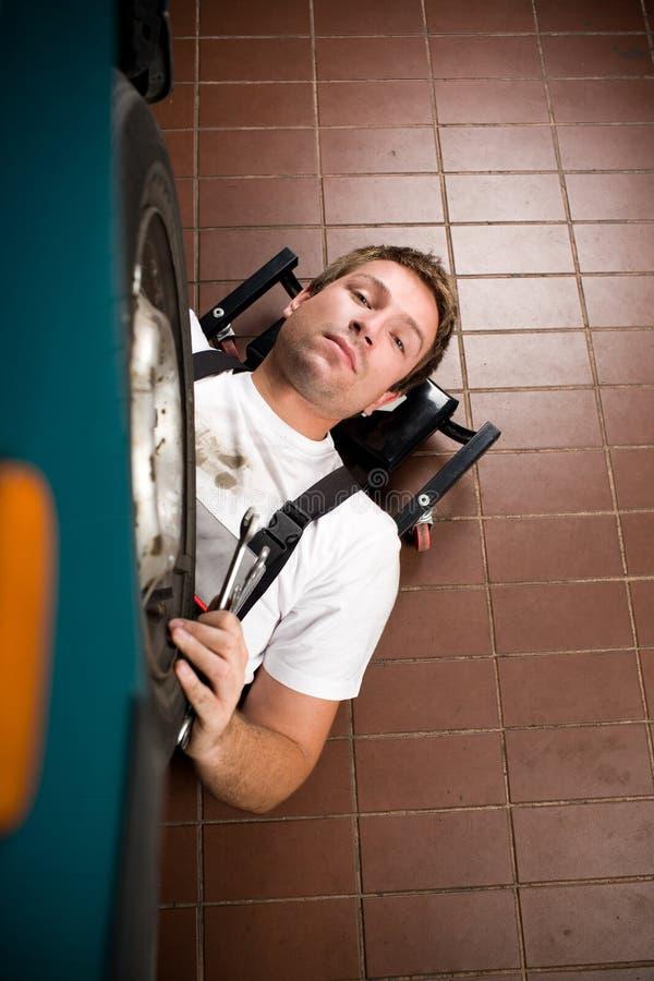 Mechaniker, der unter dem Auto arbeitet lizenzfreie stockbilder