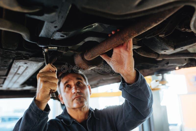 Mechaniker, der unter einem angehobenen Auto arbeitet stockfoto