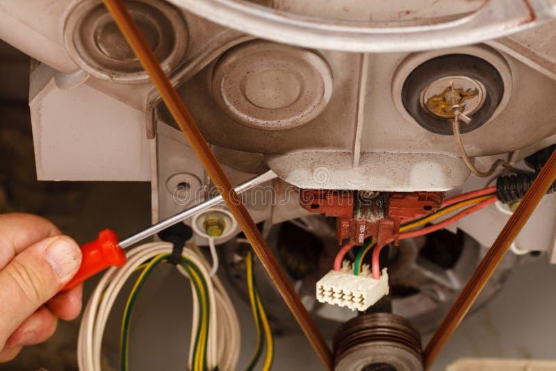 Mechaniker, der Waschmaschine repariert stockfotografie