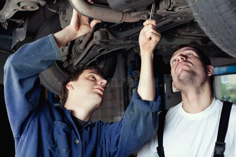 Mechaniker des Auto-zwei, der Auto repariert stockbild