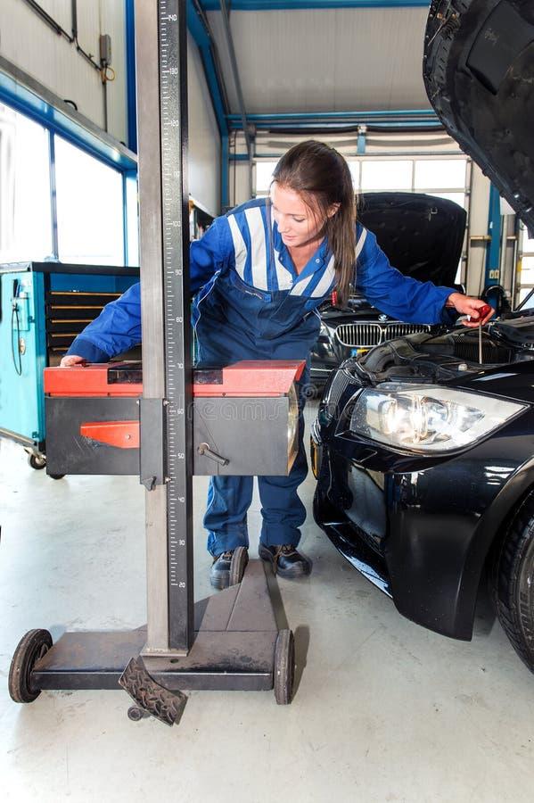 Mechaniker, die Höhe der Hauptlichter eines Autos justierend stockfotos
