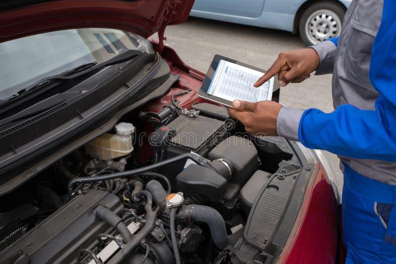 Mechaniker With Digital Tablet bei der Untersuchung des Autos lizenzfreies stockfoto