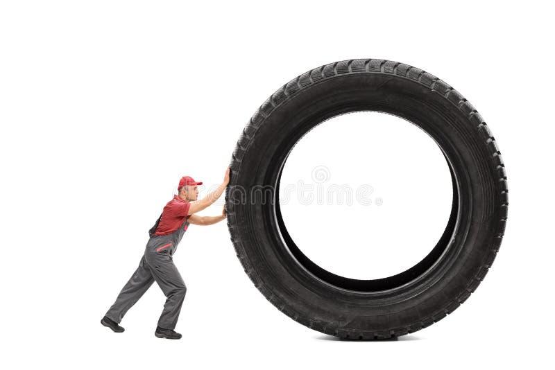 Mechaniker in einem grauen Overall, der einen riesigen schwarzen Reifen drückt stockbild
