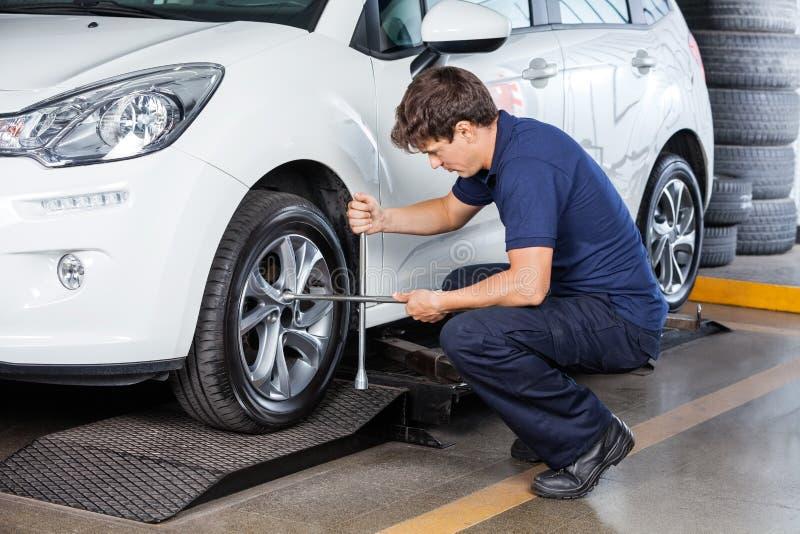 Mechaniker Fixing Car Tire an der Garage lizenzfreies stockbild