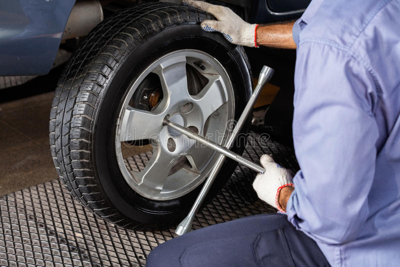 Mechaniker Fixing Car Tire mit Rim Wrench stockfotos