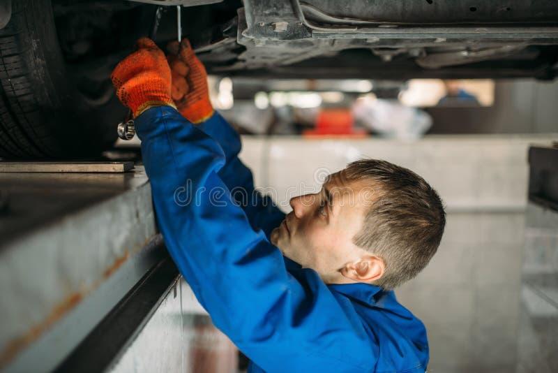 Mechaniker justiert die Radwinkel auf Stand lizenzfreies stockfoto