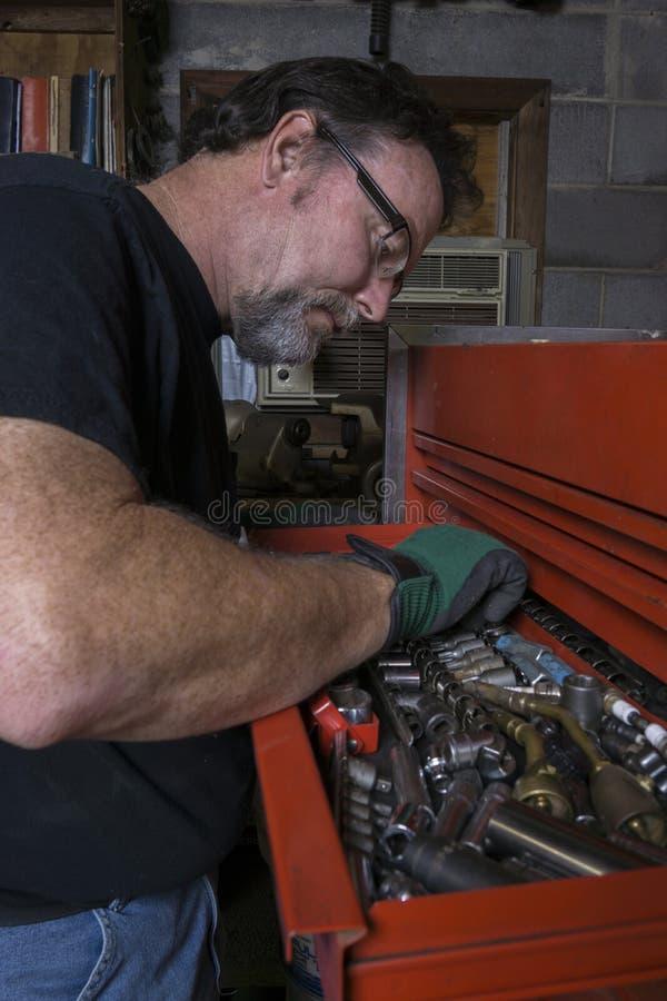 Mechaniker Looking For ein Sockel lizenzfreie stockfotografie