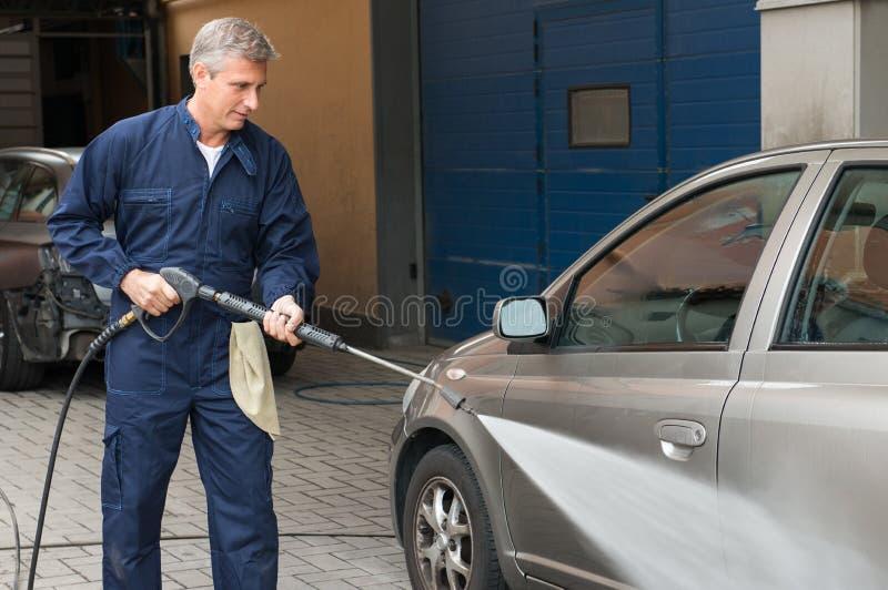 Mechaniker Man Washing ein Auto stockfotografie