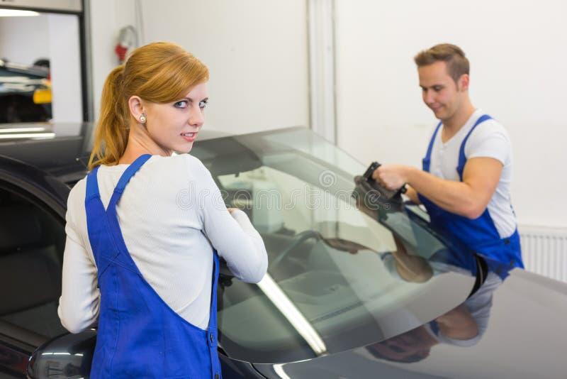 Mechaniker oder Glaser installieren Windschutzscheibe oder Windfang auf Auto lizenzfreies stockbild