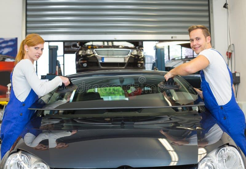 Mechaniker oder Glaser installieren Windschutzscheibe oder Windfang auf Auto stockfotografie