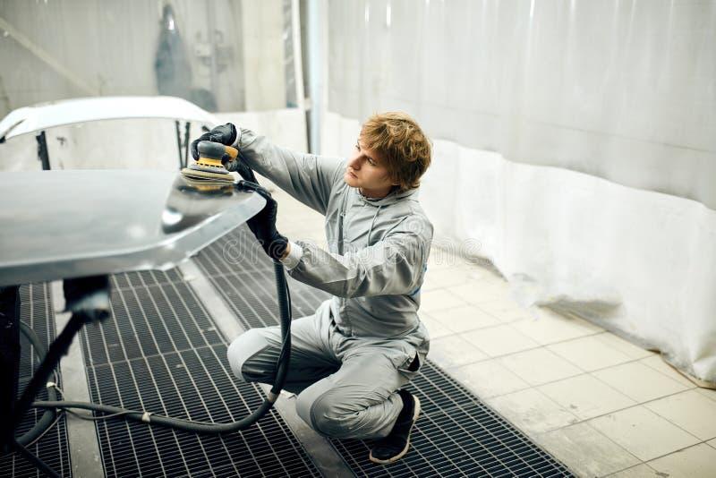 Mechaniker reibt Autoteil für das Malen Fahrzeugkarosseriearbeits-Autoreparaturfarbe nach Unfall stockfotografie