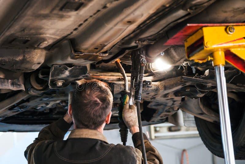 Mechaniker schweißt Schalldämpfer auf Auto durch Argonschweißen stockfotos