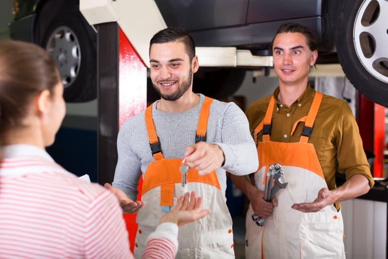 Mechaniker und Fahrer am Autoservice stockfotografie