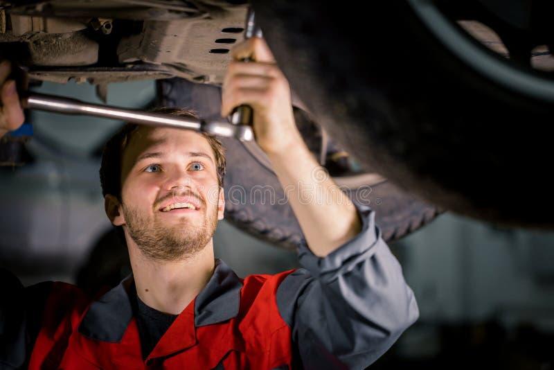 Mechaniker unter Auto in examing Reifen der Garage und in technischer Zustand lizenzfreies stockfoto