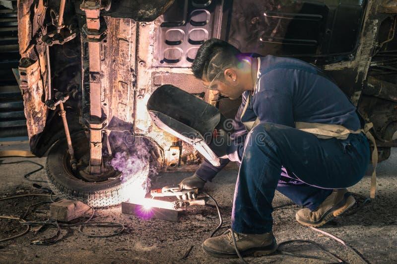 Mechanikerarbeitskraft des jungen Mannes, die alte Weinlesefahrzeugkarosserie repariert lizenzfreie stockfotografie
