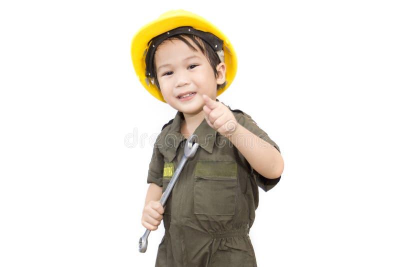 Mechanikerjunge mit Werkzeugschlüssel auf lokalisiertem weißem Hintergrund lizenzfreies stockfoto