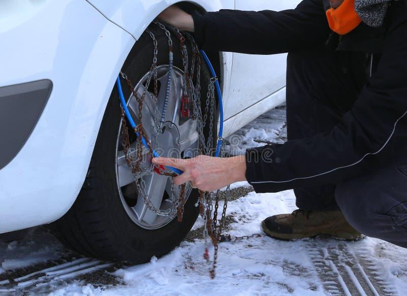 Mechanikermontage-Schneeketten im Autoreifen im Winter auf Schnee lizenzfreies stockfoto