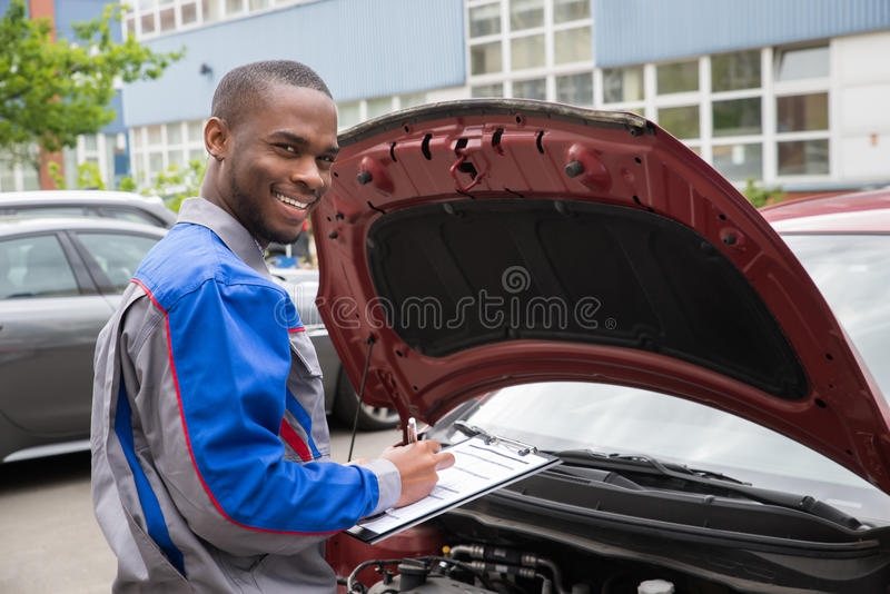 Mechanisch With Clipboard In Front Of een Auto royalty-vrije stock fotografie