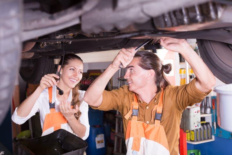 Mechanisch en medewerker die op workshop werken stock foto