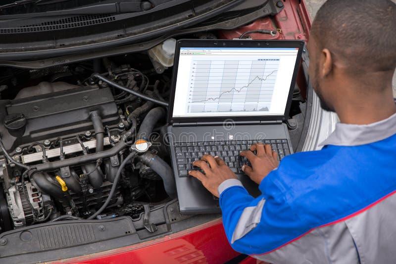 Mechanisch With Laptop While die Motor onderzoeken royalty-vrije stock afbeelding