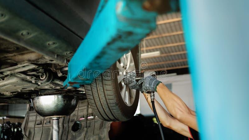 Mechanisch werk Auto op de oplaadmachine bij het station voor reparatie van de auto Fixingsservices en onderhoud stock foto