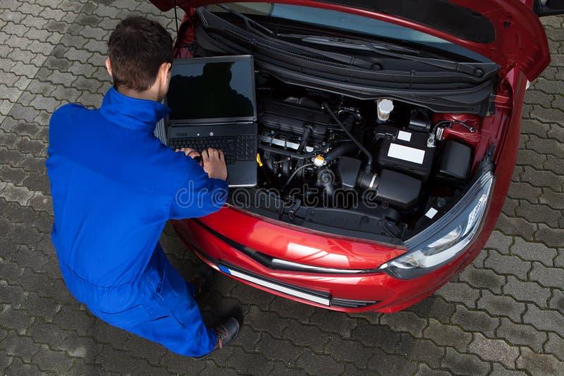 Mechanische gebruikende laptop terwijl het herstellen van auto stock afbeeldingen