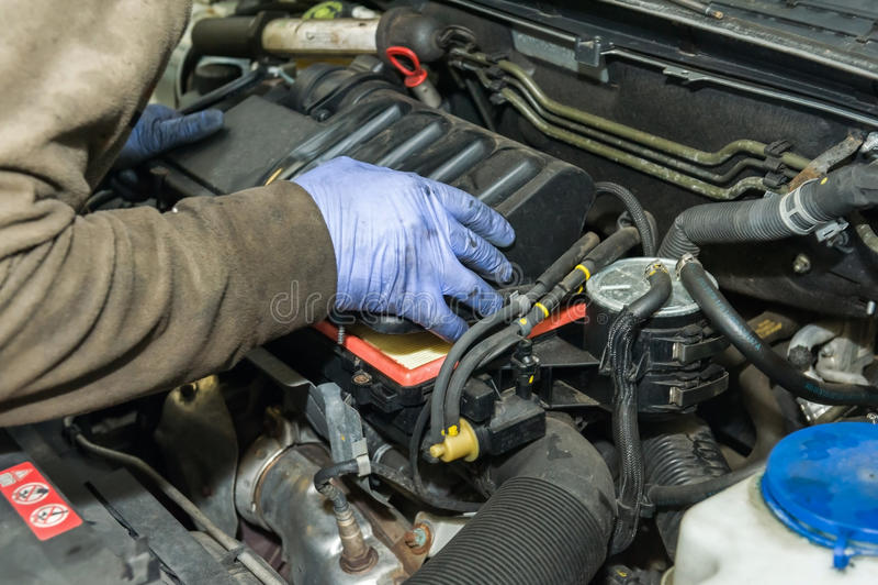 Mechanische handen op een dekking van de luchtfilter stock foto's
