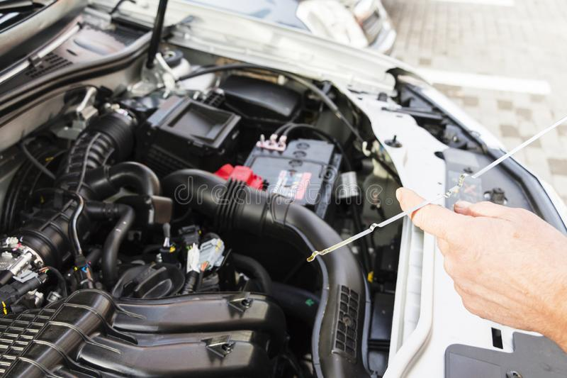 Mechanische het herstellen auto met open kap, zijaanzicht van de mechanische het controleren olie van de niveaumotor in een auto  royalty-vrije stock afbeelding