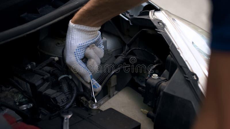 Mechanische het herstellen motor van een auto, het bevestigen automobielbatterij, breuk onder kap royalty-vrije stock afbeeldingen