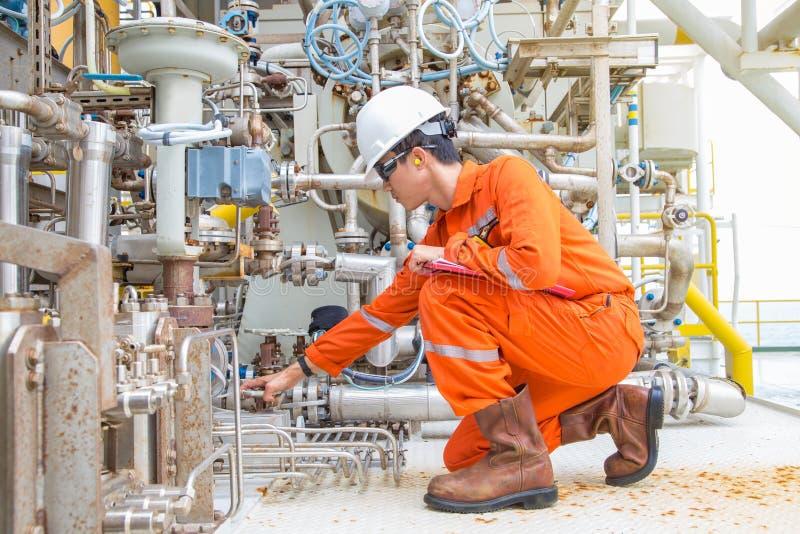 Mechanische ingenieur het controleren en inspecteert het systeem van de smeermiddelolie van centrifugaalgascompressor bij zeegasp stock foto's