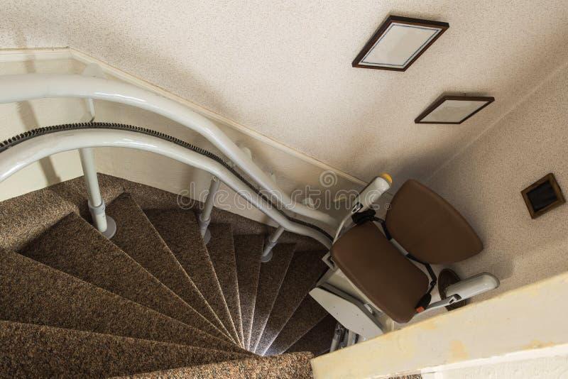 Mechanische Sesselbahn, welche die behinderten oder gealterten Leute auf und ab die Treppe älter, Stairlift für behindertes nimmt lizenzfreies stockbild