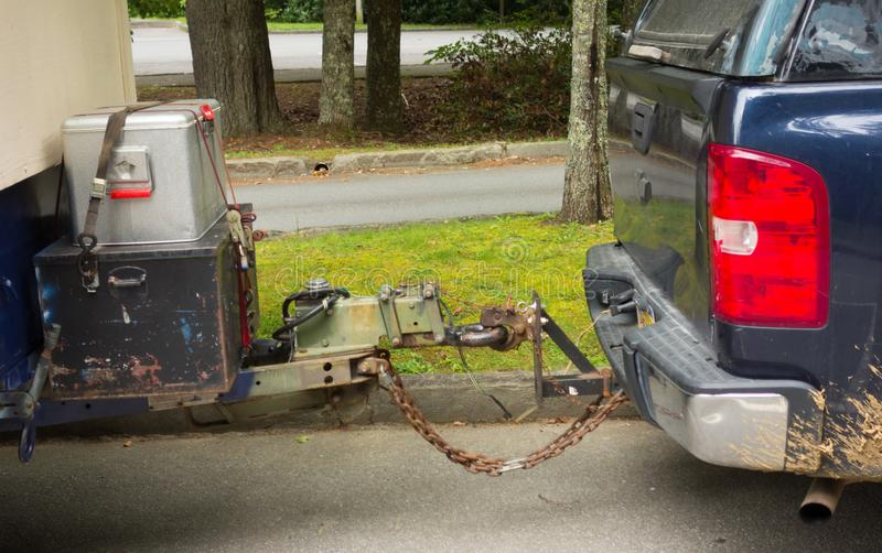 A trailer hitch with a rusting chain being used to join two vehicles together. A mechanism being used to safely pull a trailer behind a large car royalty free stock images