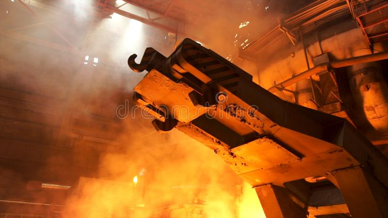 A mechanism with hooks in the hot shop with rising smoke and burning fire at the metallurgical plant. Stock footage. A mechanism with hooks in the hot shop with stock photography