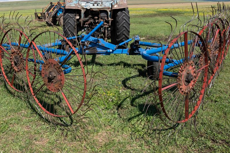 The mechanism for transferring hay during drying attached to the. Mechanism for transferring hay during drying attached to the tractor stock image
