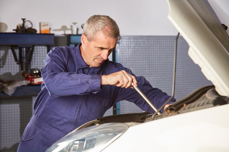 Mechatronics engineer at the repair of the car engine. Or engine tuning in the workshop stock photo